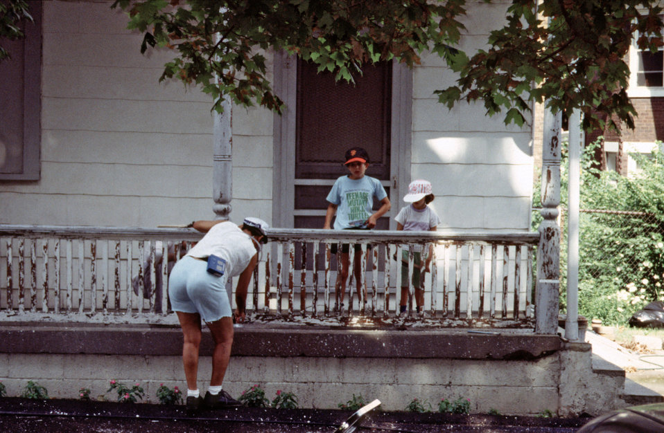 This photograph depicted a volunteer worker manually dry scraping lead-based paint from a porch railing as she prepared it to be repainted w
