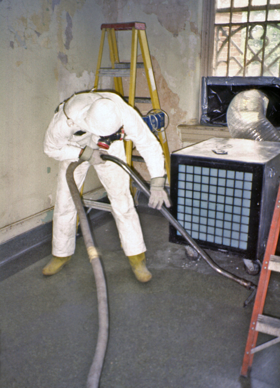 This 1991 photograph depicted a worker vacuuming lead-based paint debris with a high-efficiency vacuum equipped with a proper air filter abl