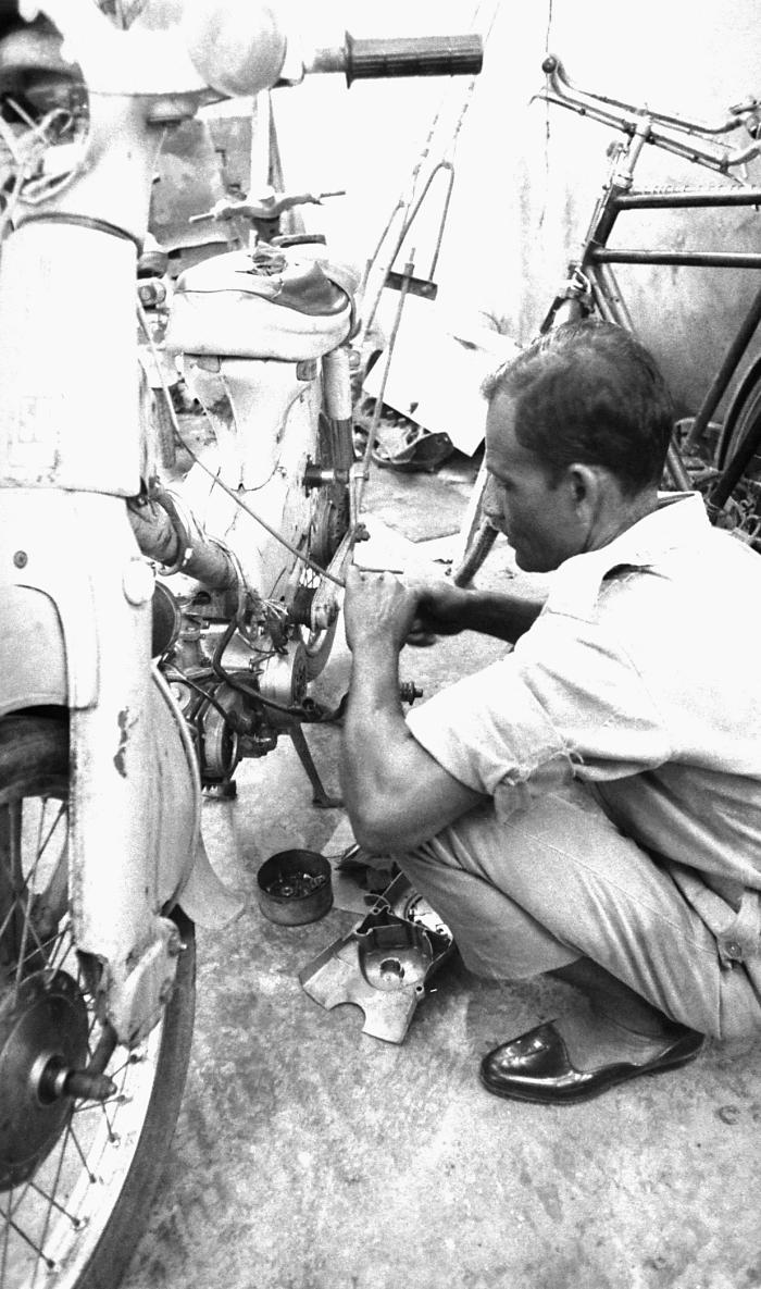 This photograph, showed a mechanic at work repairing a motor scooter located at the E.I.S., and public health personnel headquarters known a