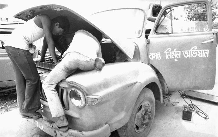 This photograph, showed two mechanics at work repairing a truck located at the E.I.S., and public health personnel headquarters known as 'Sm