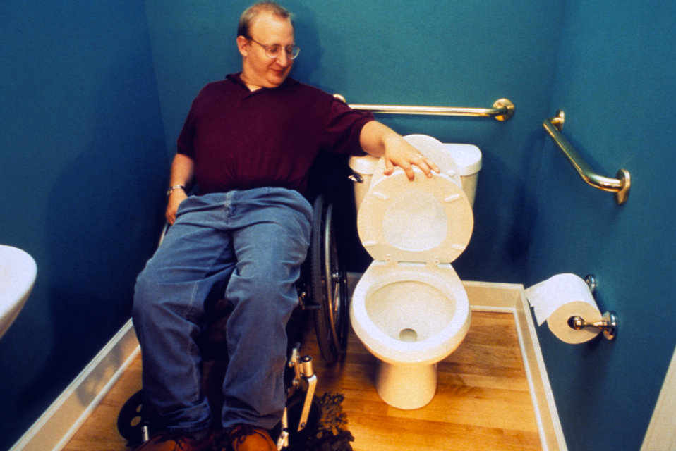 This 1995 image depicted a mobility-challenged man who was sitting in a wheelchair next to a toilet inside a residential, two-fixture bathro