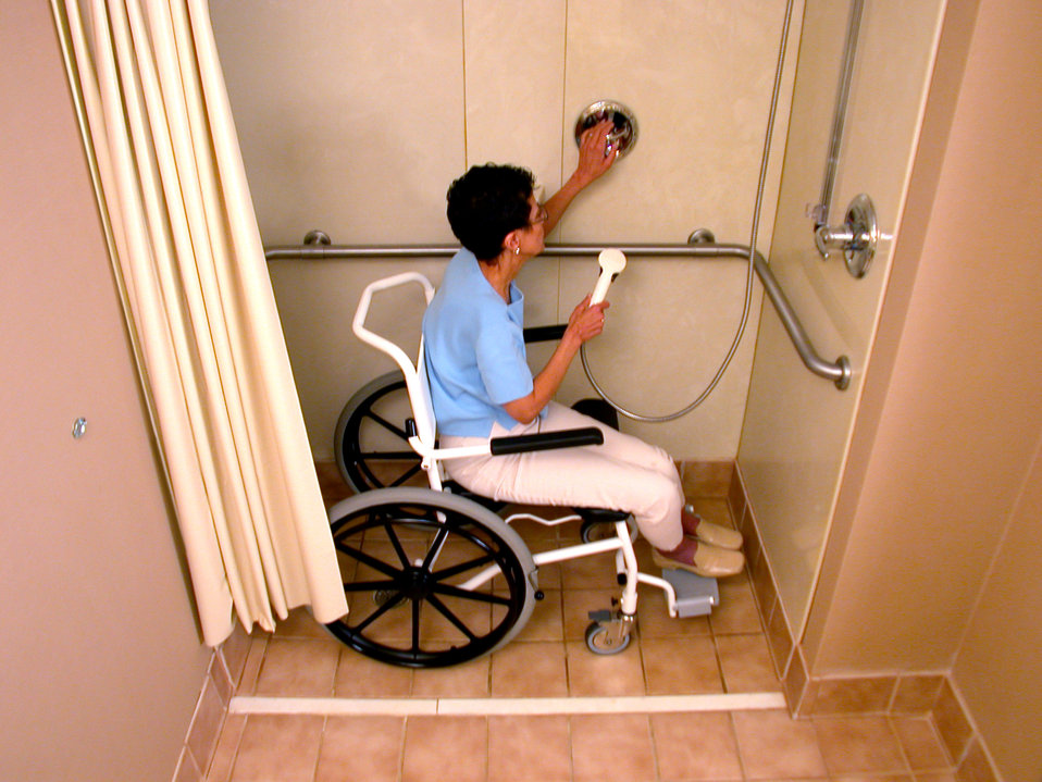 This 1995 image depicted a mobility-challenged woman who was sitting in a wheelchair in a medium-sized 'curbless' shower, as she was demonst