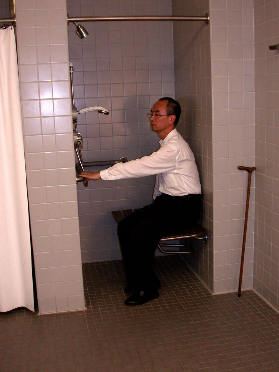 This image showed a man sitting on a folding, wall mounted seat in the down position inside a small 3' x 3', 'curbless' shower. The person w