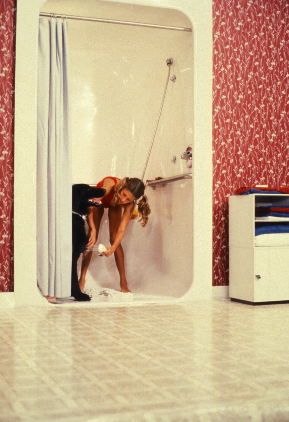 This was one of two images (PHIL# 9195 - 9196), depicting the usage of a white fiberglass 'curbless' shower stall, which was a single piece,