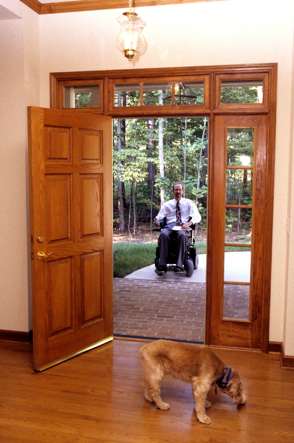 This 1996 image depicted a man seated in his motorized wheelchair just outside his home, and was about to pass inside through his opened fro