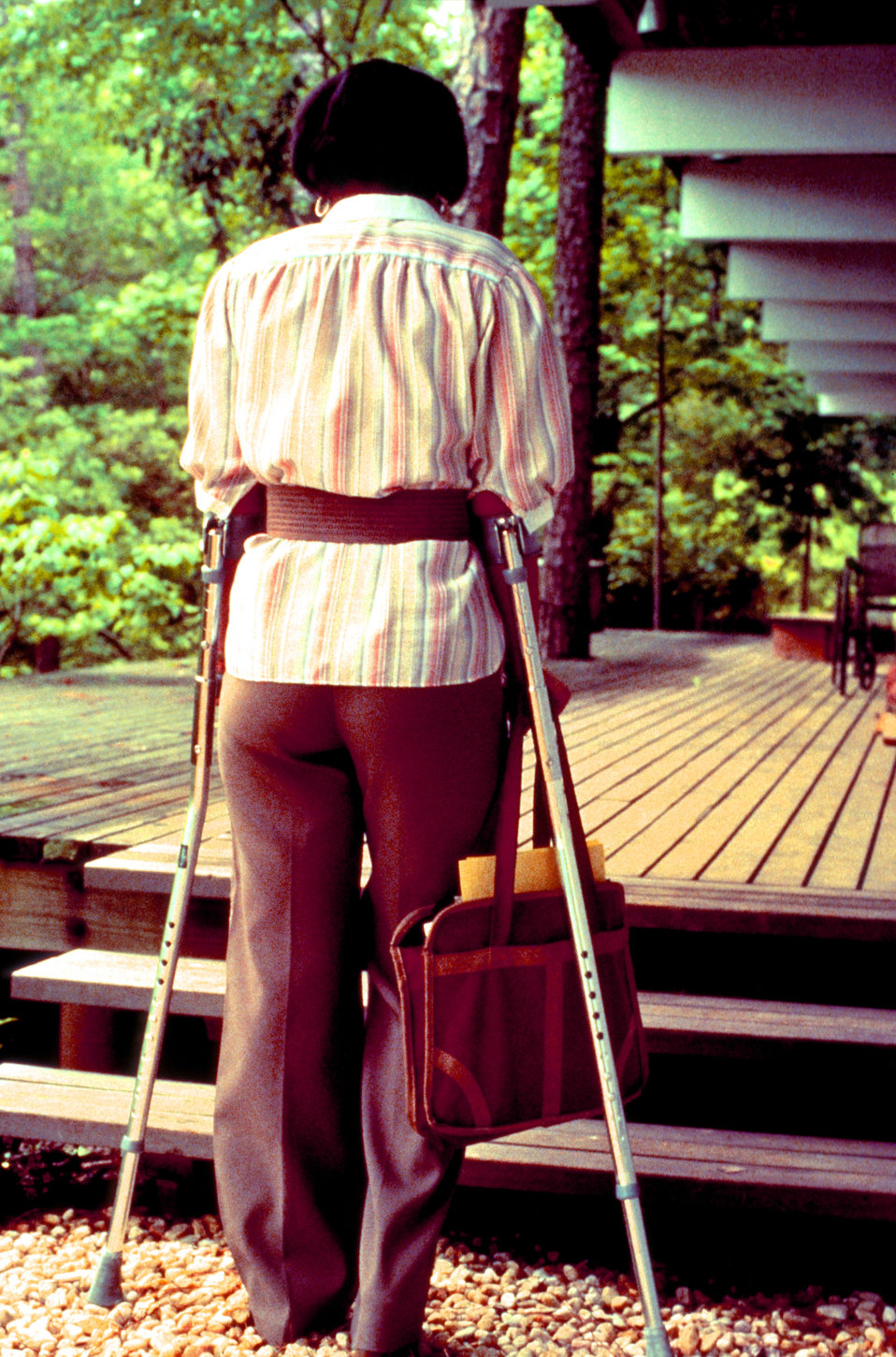 In an attempt to ascend to the next level of a wooden deck, this woman, who at the time was in need of crutches, was about to attempt her as