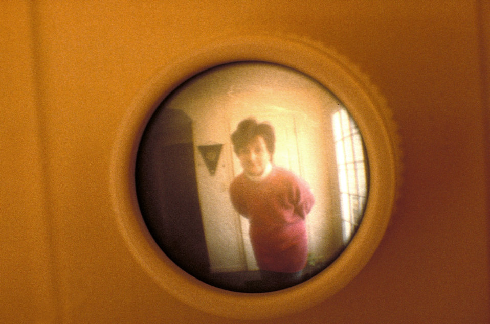 This 1995 photograph depicted a close up view from inside a front door through its very wide, wide-angle peep hole. The image revealed the m
