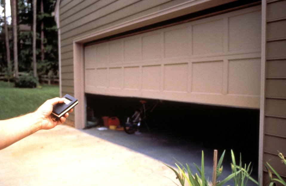 This 1994 image depicted a person opening and closing a remotely controlled electro-mechanical garage door. Such controllers were some of th