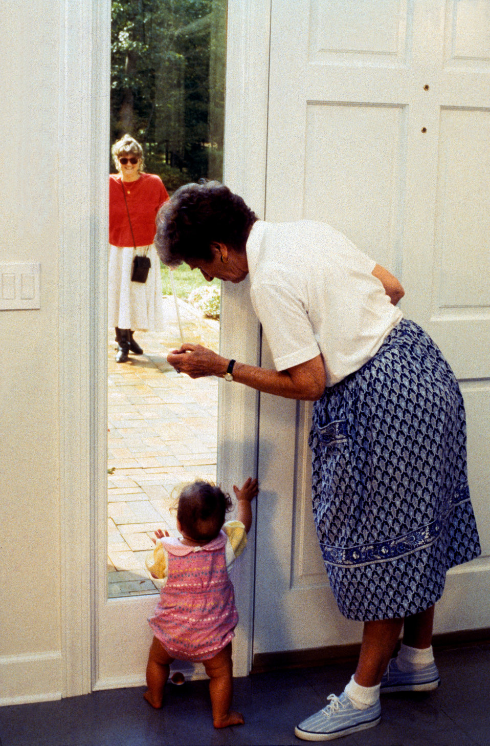 This 1996 image depicted a grandmother with her granddaughter as they were standing at the front door to their home, and looking out through