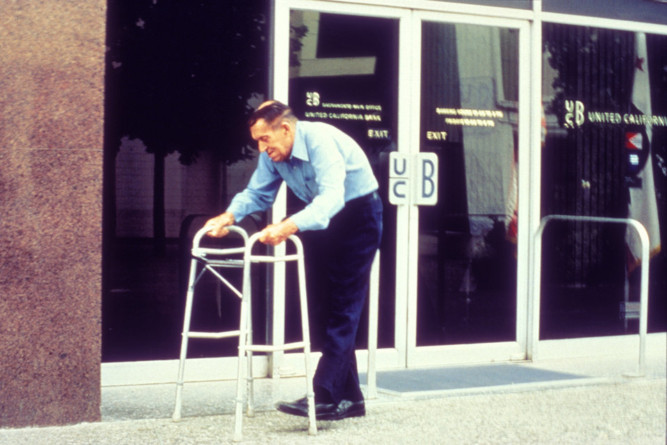 This 1990 image depicted a man who was using walker while traversing a public sidewalk. The path was 'smooth', but not slick, which is espec