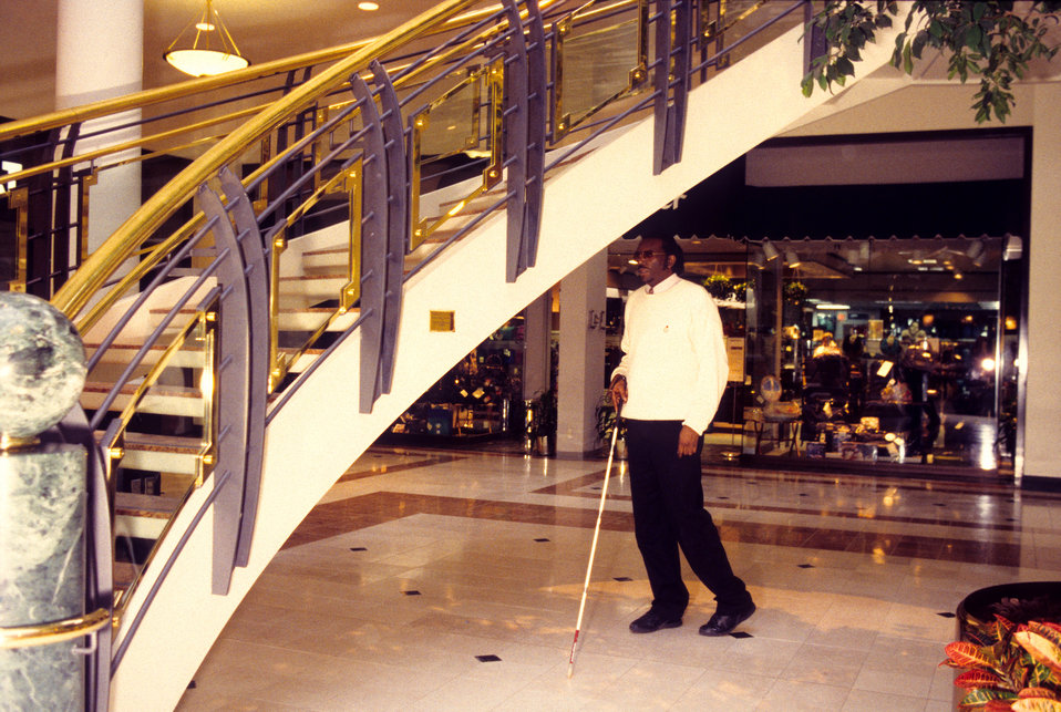 This 1996 image depicted a blind man who was walking inside a mall with the use of a walking cane. Note the dangerously low staircase with i