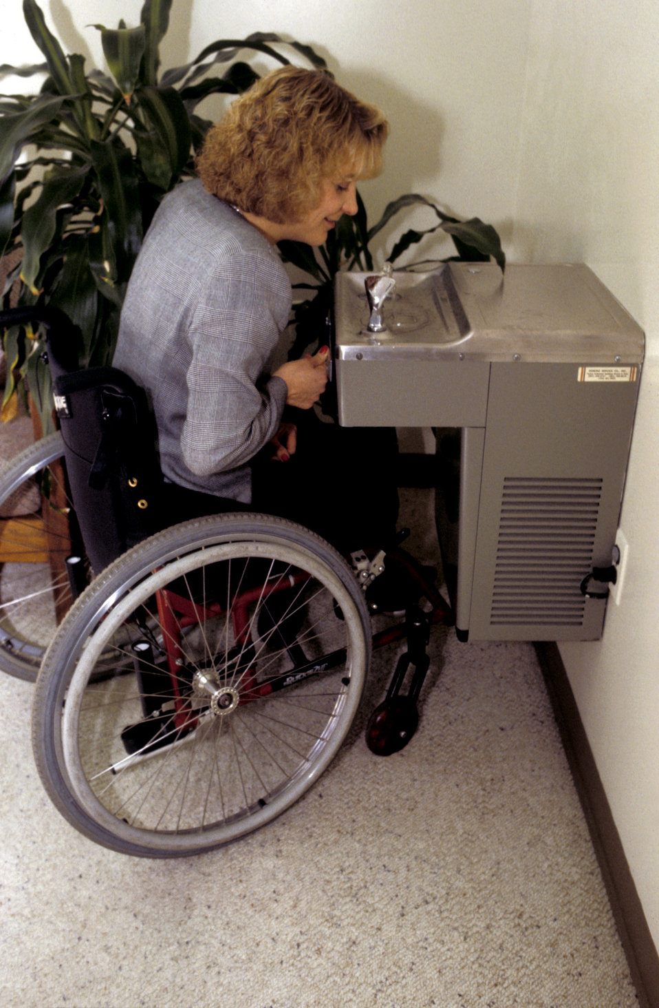 In this 1998 image, a wheelchair-seated woman was about to drink from a stainless steel water fountain which offered two spouts arranged at