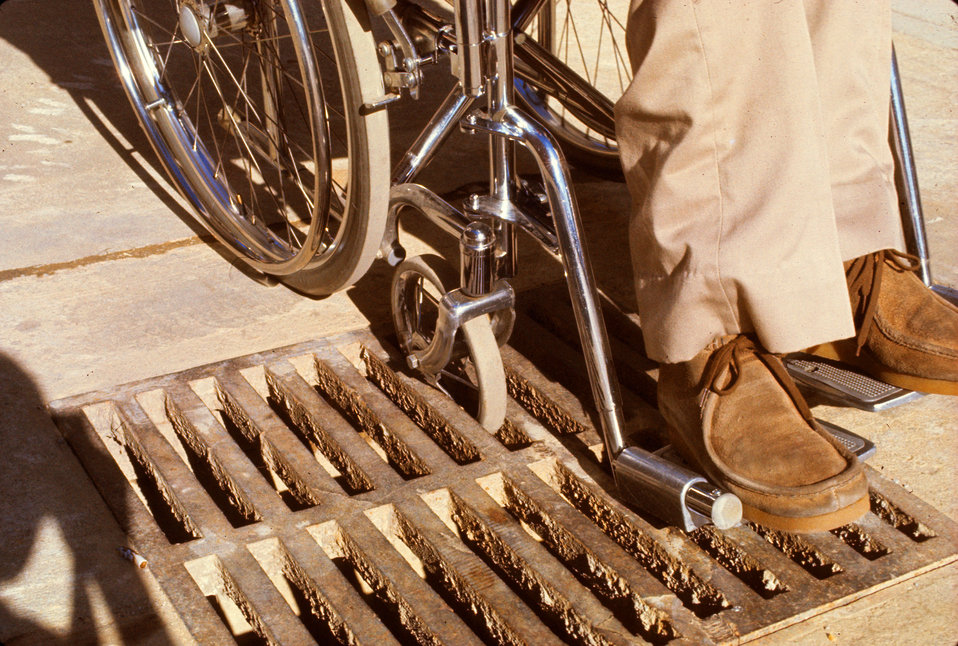 As noted in PHIL 9056, this drainage grate was not designed with the mobility-challenged, wheelchair-seated user in mind. One of the smaller