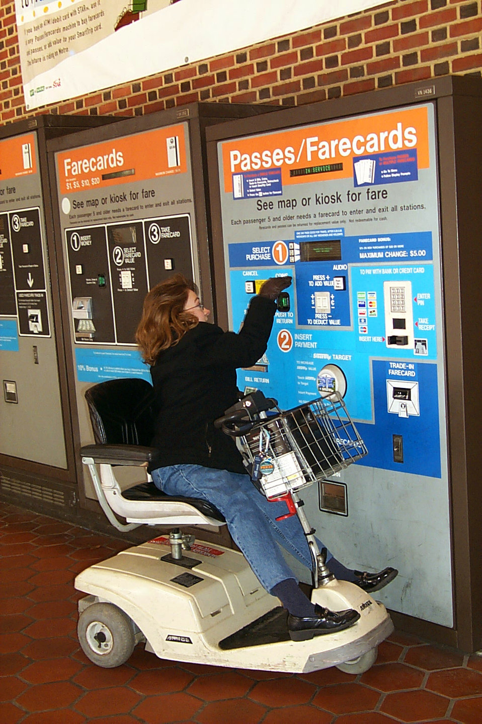Depicted in this 2004 image was a wheelchair-seated woman who was in the process of purchasing a ticket from an automatic ticket dispensing