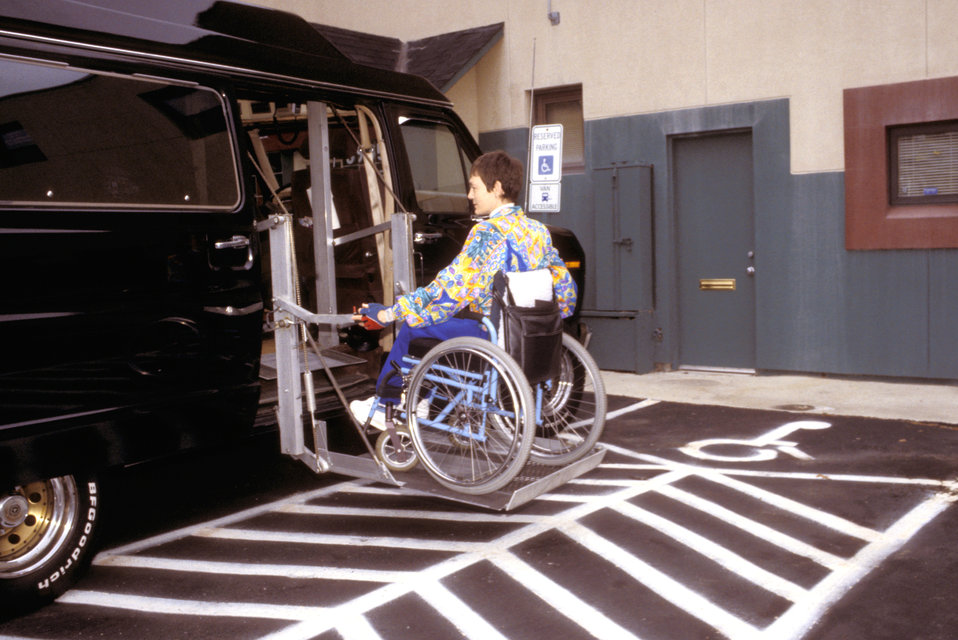 This was the second of six images (PHIL# 9068 - 9073) depicting a wheelchair-seated woman in the process of exiting a wheelchair lift-equipp