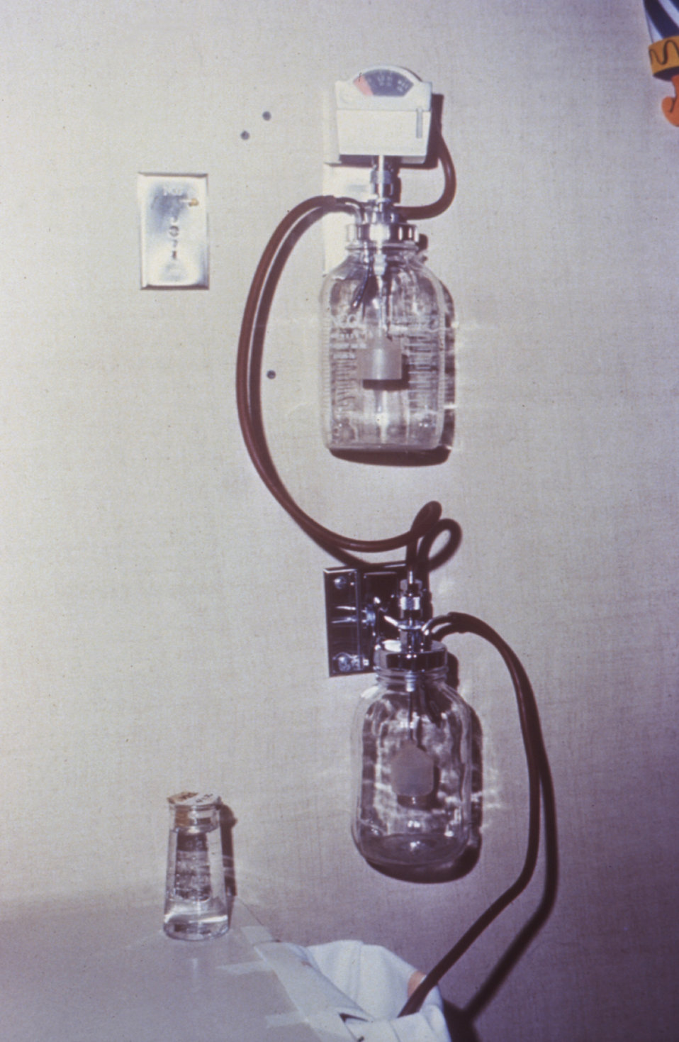 This is a 1970 photograph inside a hospital room depicting a wall-mounted suction bottle.