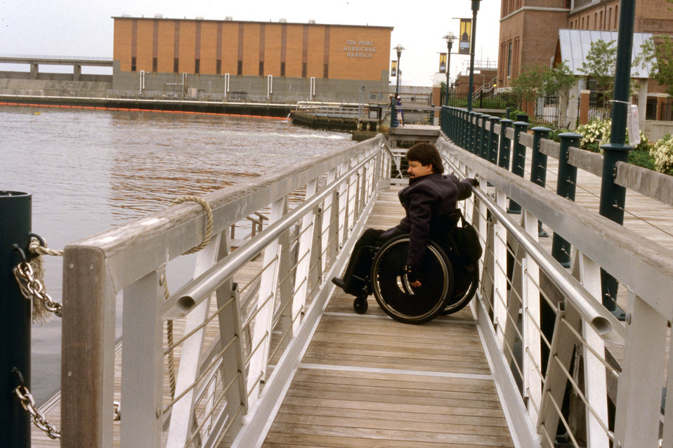 In this 2003 image, a wheelchair-seated man was positioned upon a ferry terminal dock, while awaiting the arrival of the ferry transport. No