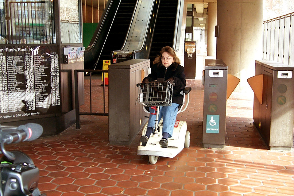 In this 2004 photograph, a motorized scooter-bound woman was in the process of passing through the turnstile portal leading away from the di