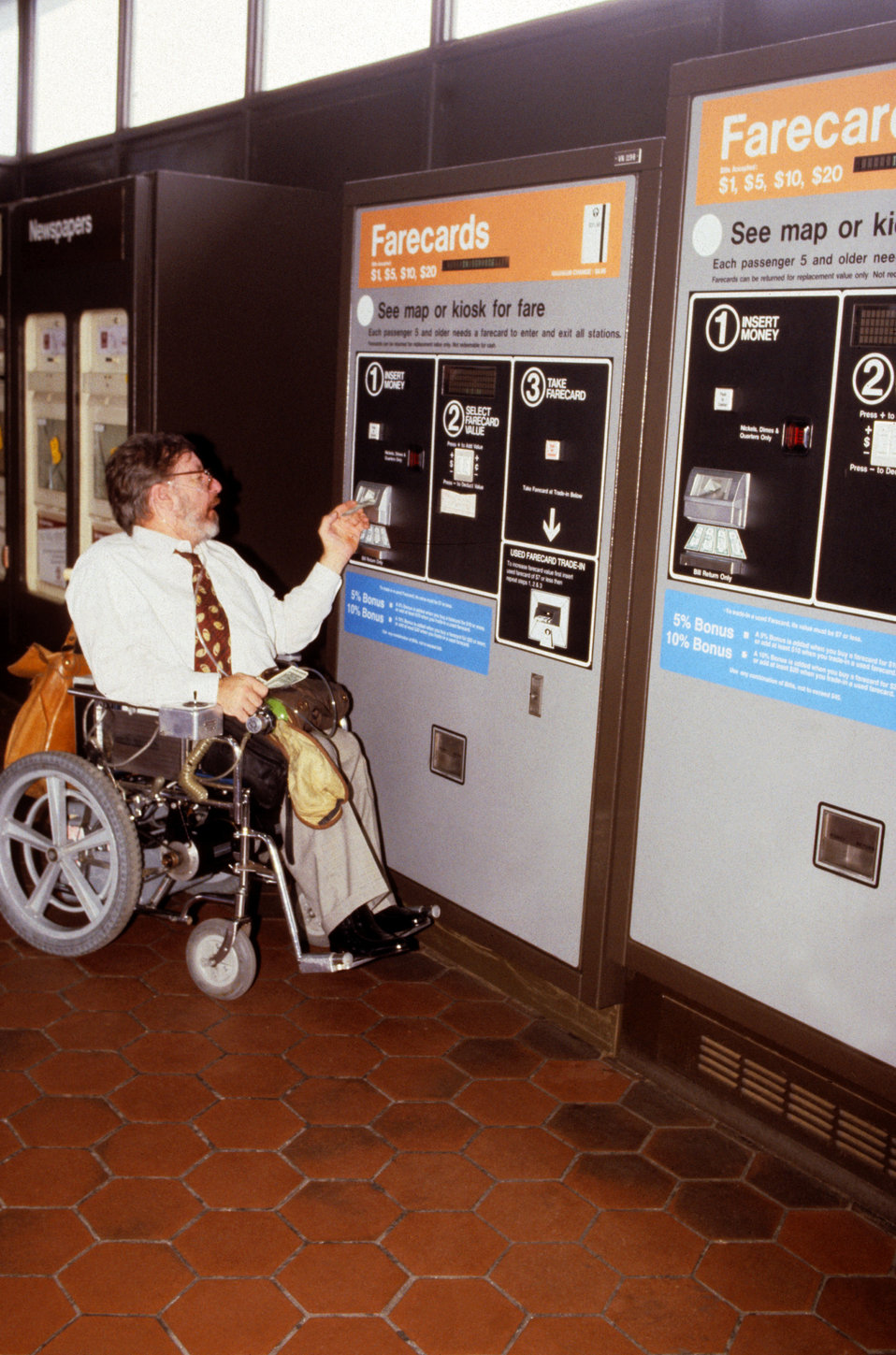 Depicted in this 2004 image was a wheelchair-seated man who was in the process of purchasing a ticket from an automatic ticket dispensing ma