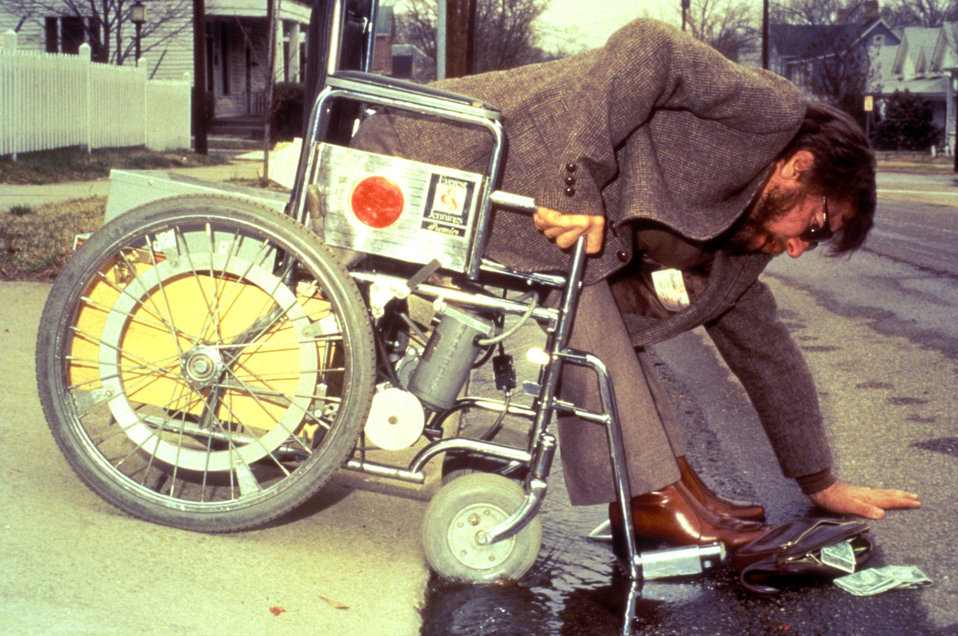 This 1984 photograph depicted a wheelchair-bound man, who while crossing a roadway, had dropped his wallet, which he was attempting to pick