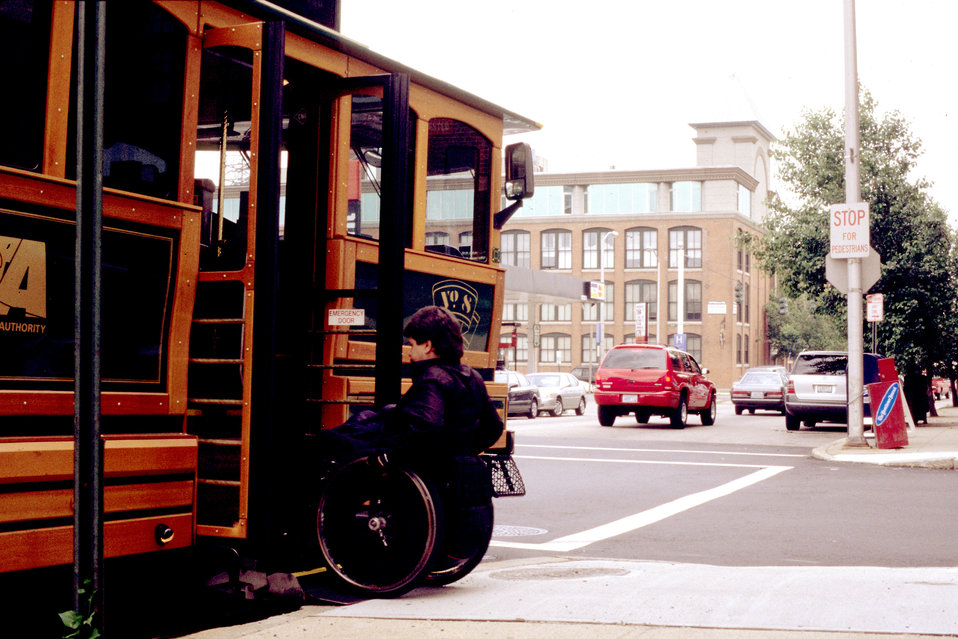 The wheelchair-seated man in this photograph was in the process of boarding an antique-style, faux trolley city bus, by using a lift mechani