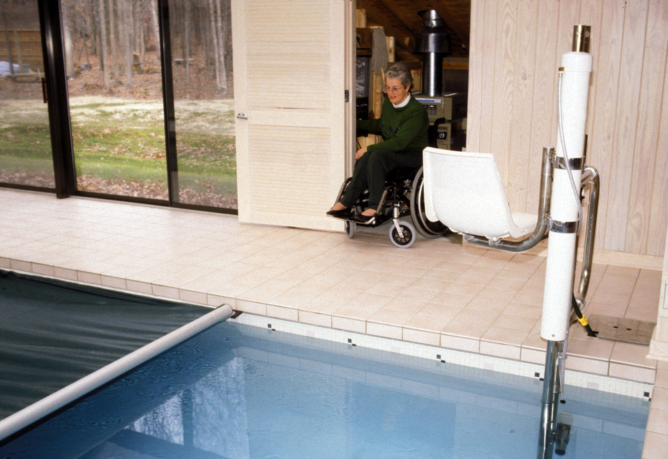 In this 1993 image (and see PHIL# 9086), a woman seated in her wheelchair was about to enter a publicly-accessible swimming pool by using a
