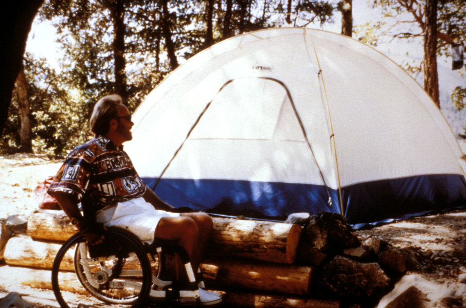 This 1995 image depicted a man seated in his wheelchair that was positioned in front of a log retaining wall with a domed tent in the backgr