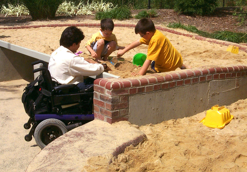 In this 2000 image (and see PHIL# 9084), a father seated in his wheelchair, was playing with his two sons who were building sand castles in