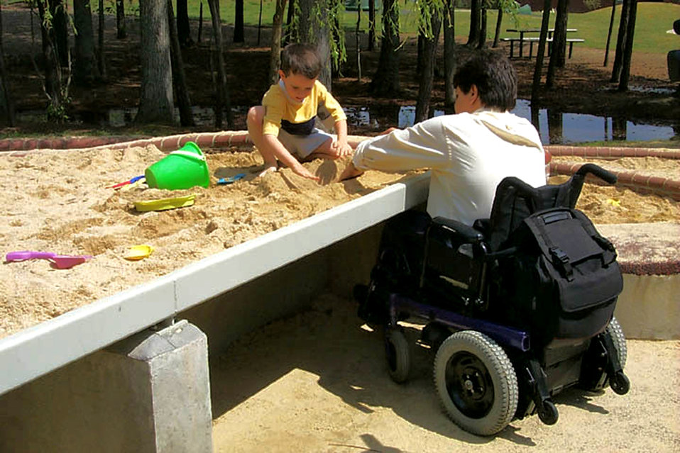 In this 2000 image (and see PHIL# 9083), a father seated in his wheelchair, was playing with his son who was building sand castles in a publ