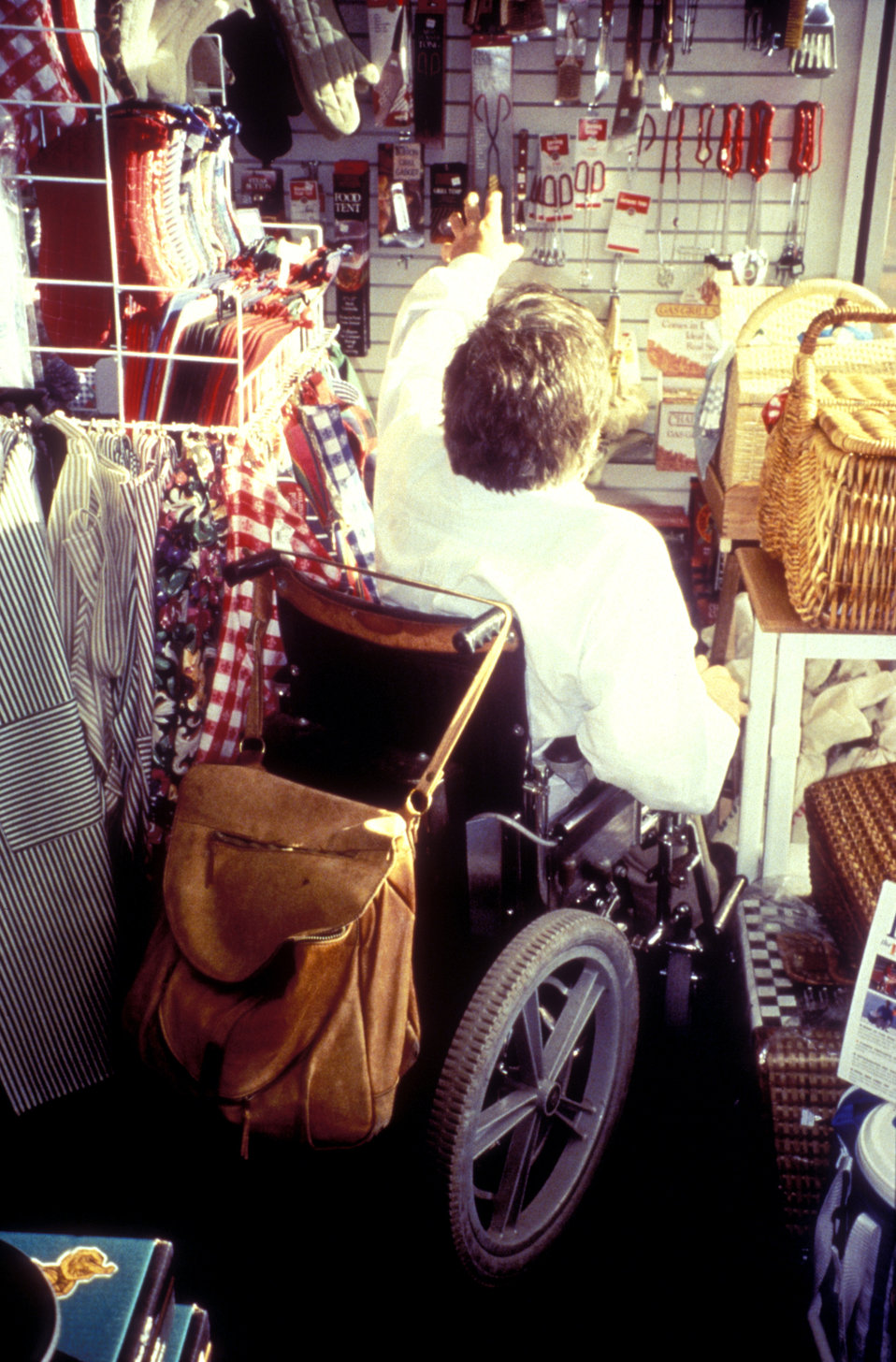 This 1988 image depicted a man seated in his motorized wheelchair, while browsing a retail store's inventory, which appeared to be cooking a
