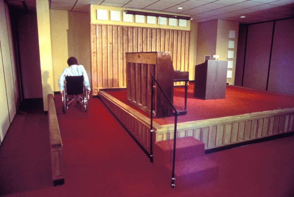 This 1990 image depicted a man using a wheelchair in order to traveling up a ramp to a stage area of a performance setting. Nearby stairs we