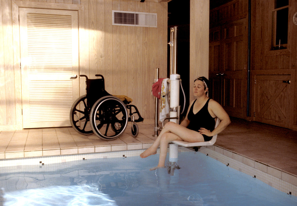 In this 1993 image (and see PHIL# 9085), a woman seated in her wheelchair was about to enter a publicly-accessible swimming pool by using a