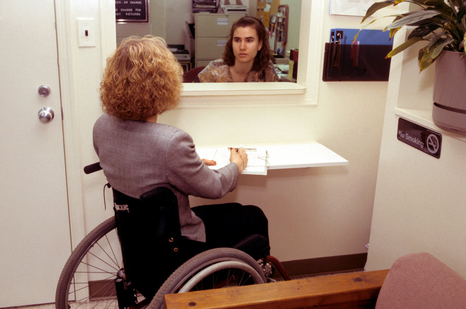 Depicted in this 1994 image, a woman who was seated in her wheelchair, had approached an office receptionist, and was conversing with her th