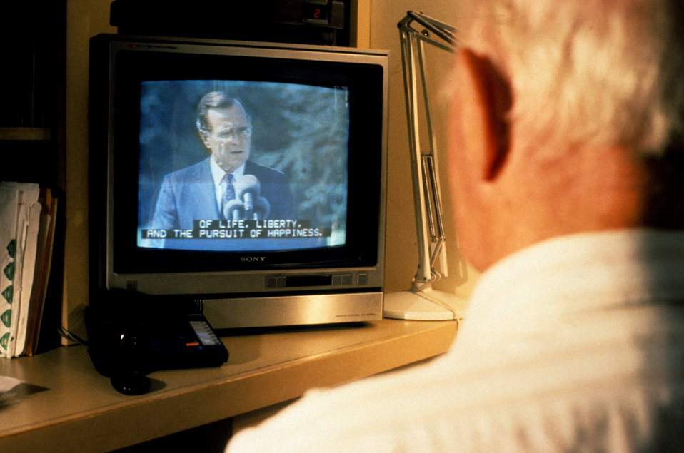 This 1995 image depicted an elderly man as he was watching a TV that had been configured to display text captioning, which could be viewed a