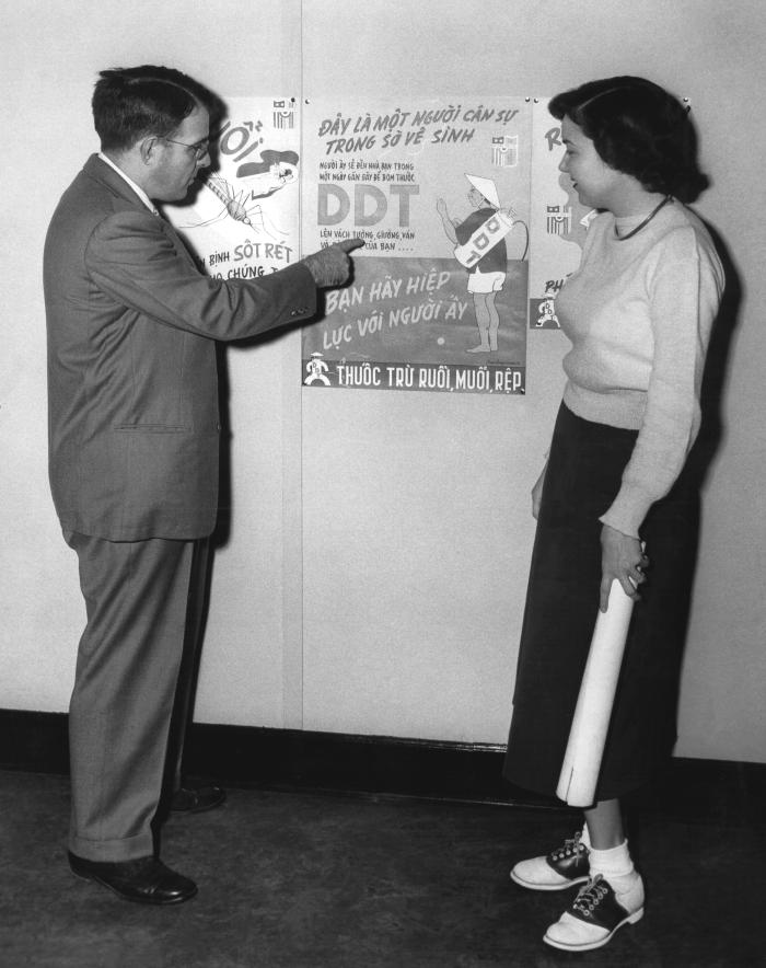 This photograph shows CDC medical entomologist Dr. Harry D. Pratt describing a DDT poster used in a Malaria Control Program.