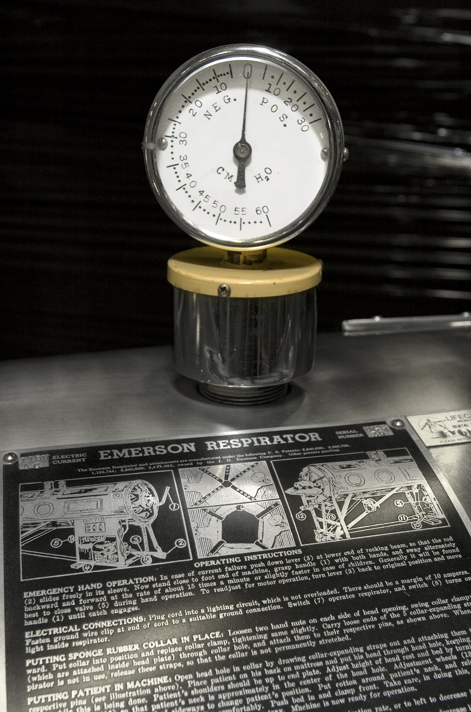 This photograph depicts the pressure gauge that sits atop of an Emerson model mechanical ventilation system, or iron lung.