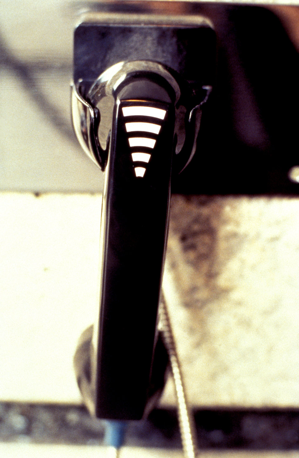 This 1995 photograph depicted a telephone receiver handset that had been equipped with a volume control, as well as the universal symbol for
