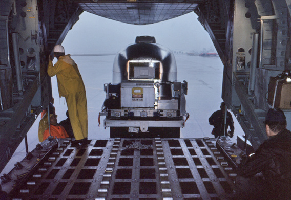 This 1976 photograph showed technicians that were loading a mobile quarantine facility (MQF) into an aircraft that was on its way to Atlanta