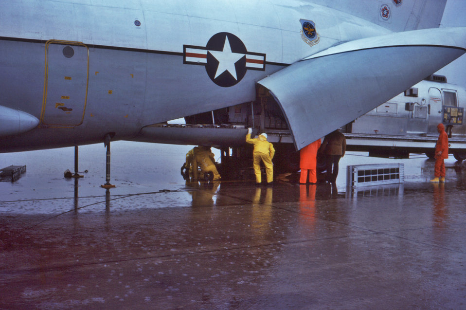 This 1976 photograph showed several loadmasters, as they were loading the CDC's mobile quarantine facility (MQF), into an aircraft to be tra