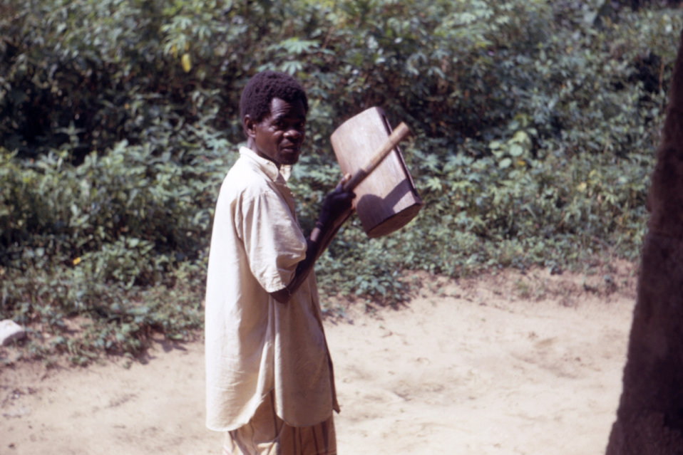 This Nigerian volunteer was using the sound of a drum to announce to refugees within a Biafran war relief camp that food was ready for distr