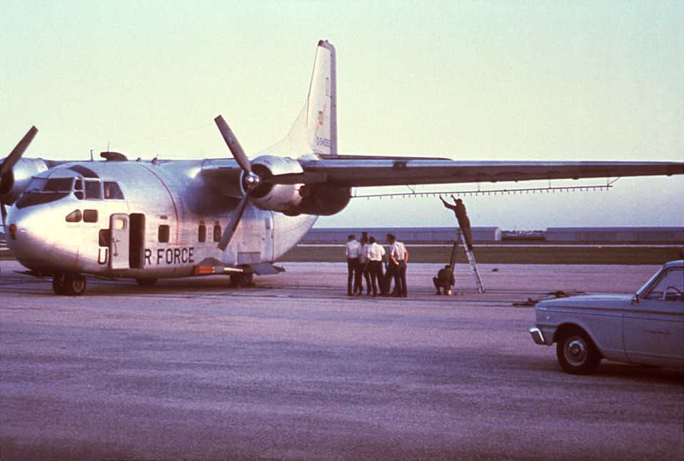 This photograph depicts a C-123 USAF aircraft, which was being outfitted with an insecticidal spray apparatus in order to combat an outbreak