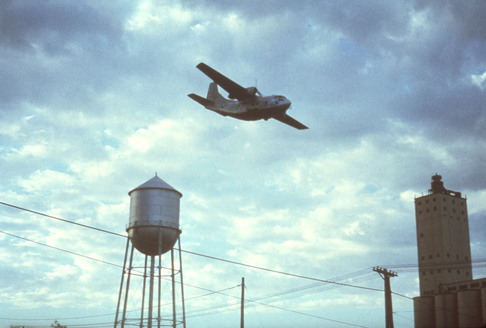 This 1981 photograph depicts a C-123 USAF aircraft dispersing an insecticidal spray over Plainview, Texas in order to combat a troublesome i