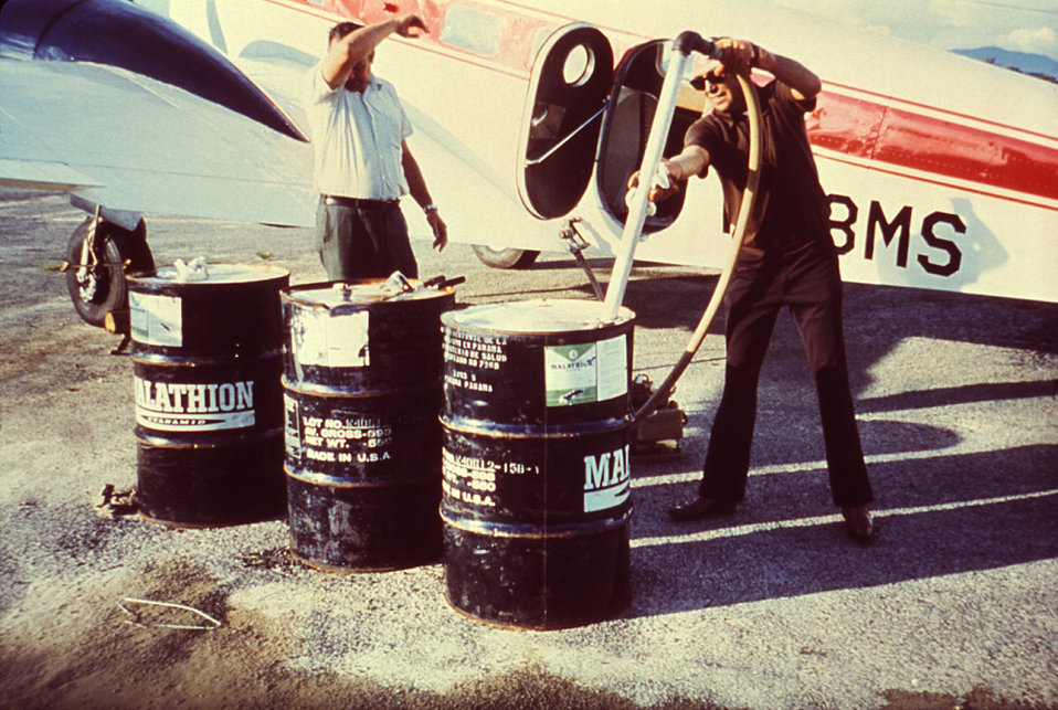 This 1981 photograph depicts two field technicians filling the pump mechanism onboard a twin-engine Beechcraft used in the dispersal of ultr
