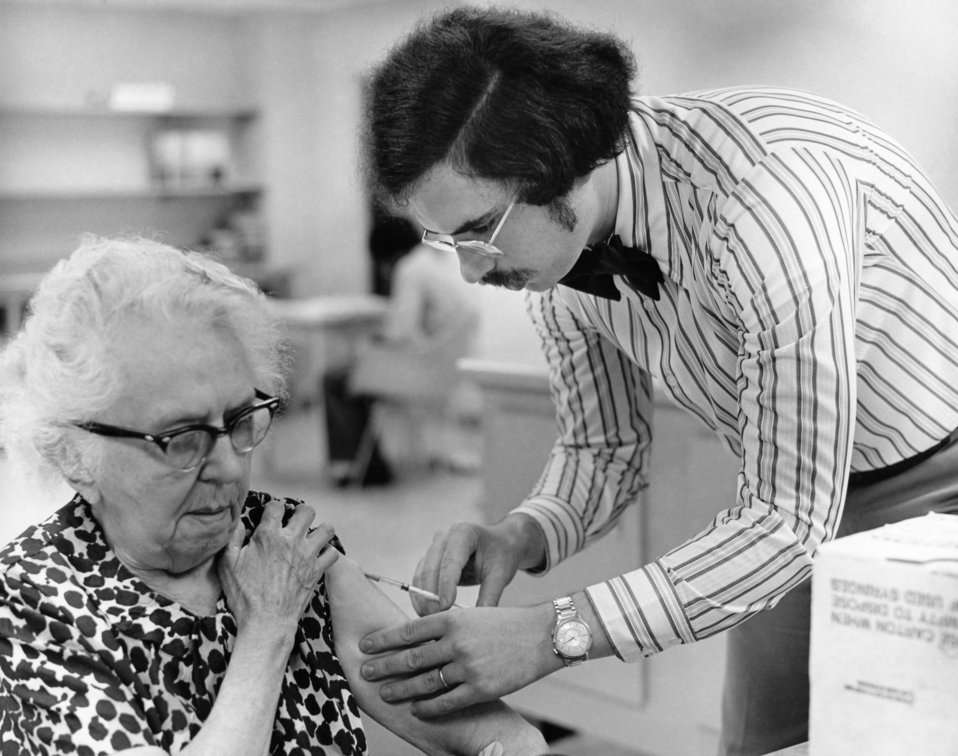This 1976 photograph showed an elderly female as she was receiving a vaccination by a public health clinician during the nationwide swine fl