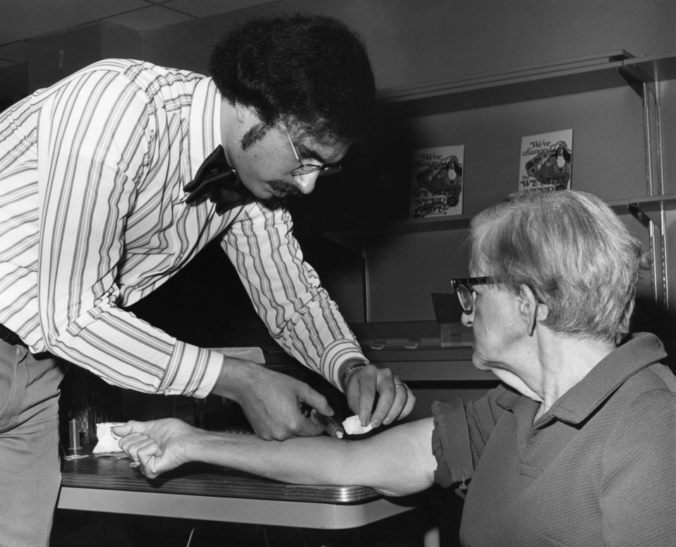 This 1976 photograph showed a health professional as he was drawing blood from an elderly man for testing during the nationwide swine flu va