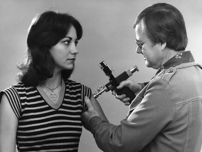 This 1976 photograph showed an adult female receiving a vaccination that was administered by a public health clinician, by way of a jet inje