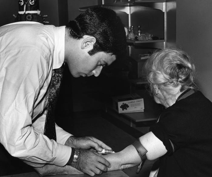 This 1976 photograph showed a public health professional drawing blood from an elderly woman, which would be tested during the nationwide sw