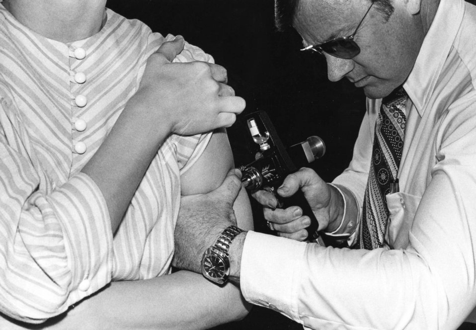 This 1976 photograph showed an adult receiving a vaccination with a jet injector during the swine flu nationwide vaccination campaign, which