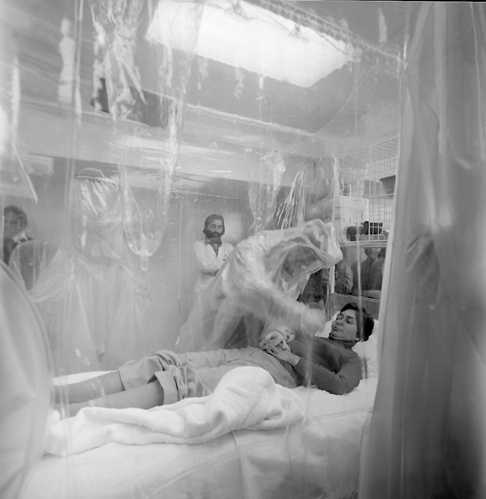 This 1981 photograph depicts a virtual patient in a Vicker's Isolation Unit.
