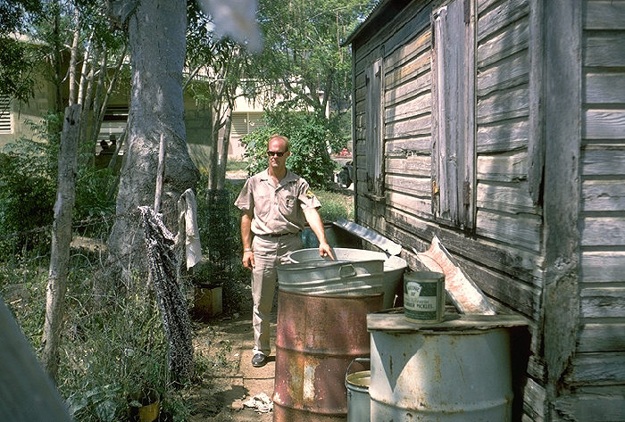 Robert Walsh by rain barrels, potential mosquito breeding site, St. Johns, Virgin Islands.